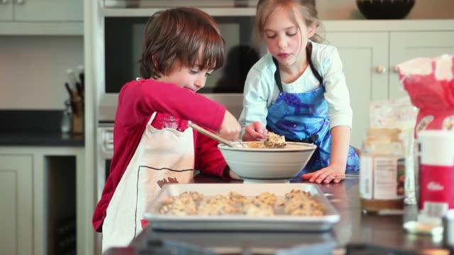ms focusing boy (8-9) and girl (6-7) putting cookie batter on baking sheet, yarmouth, maine, usa - baking sheet stock videos & royalty-free footage
