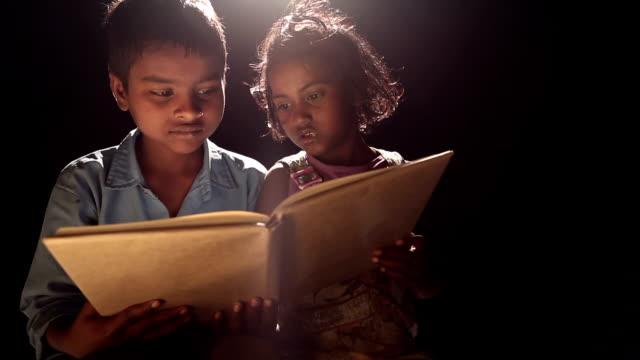 vídeos de stock e filmes b-roll de boy and girl reading a book - pobreza