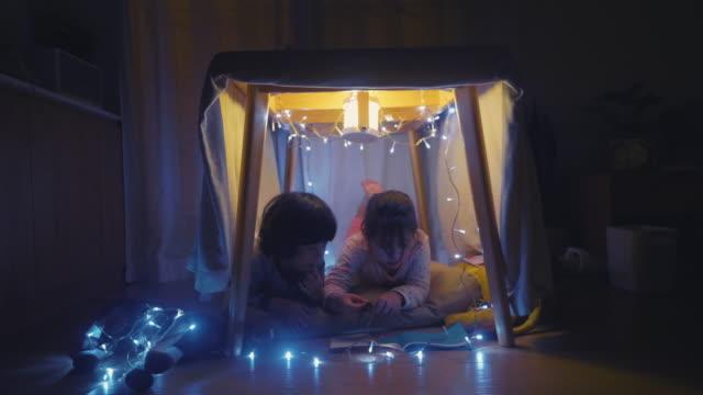 junge und mädchen lesen buch in hausgemachten zelt in der nacht - vorlesen stock-videos und b-roll-filmmaterial
