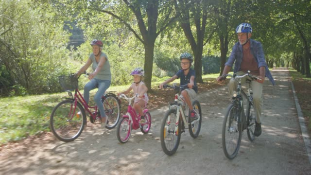 DS Boy and girl riding bikes in the park with their grandparents on a sunny day