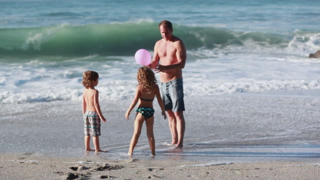 vidéos et rushes de ms ts boy and girl run to dad who has balloon then girl trips and falls and dad throws balloon and boy plays with it on beach / montezuma, puntarenas, costa rica - kelly mason videos