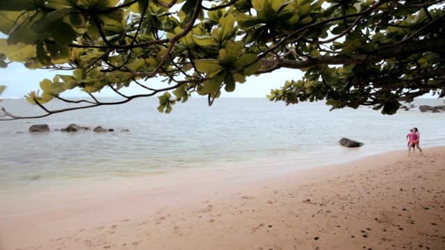 WS PAN Boy and girl running along beach at sunset / Anini, Kauai, Hawaii, USA