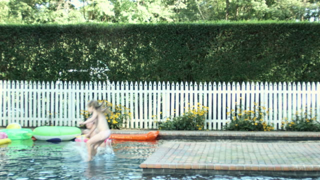 boy and girl running and jumping into swimming pool, slow motion - entstehung stock-videos und b-roll-filmmaterial