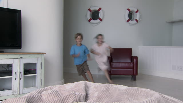 boy and girl running and jumping onto beanbag, smiling and waving at camera - bean bag stock videos & royalty-free footage