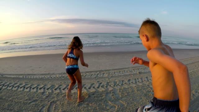 boy and girl running into ocean