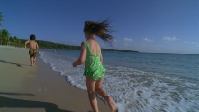 ws, boy and girl (6-7) running on beach, rear view, vieques, puerto rico - tropical climate stock videos & royalty-free footage