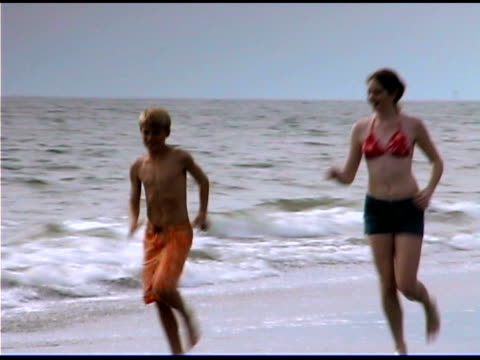 boy and girl running on beach - see other clips from this shoot 1335 stock videos and b-roll footage