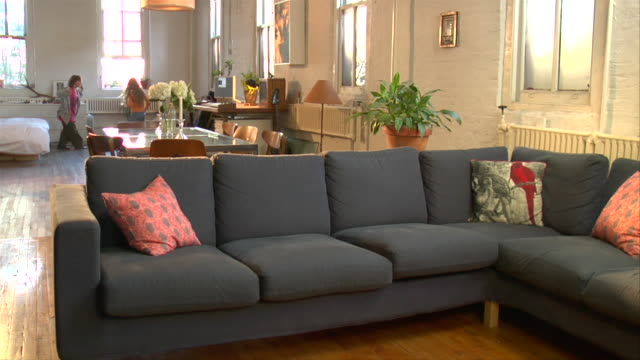 MS, SLO MO, Boy (8-9) and girl (10-11) running through living room, jumping onto sofa