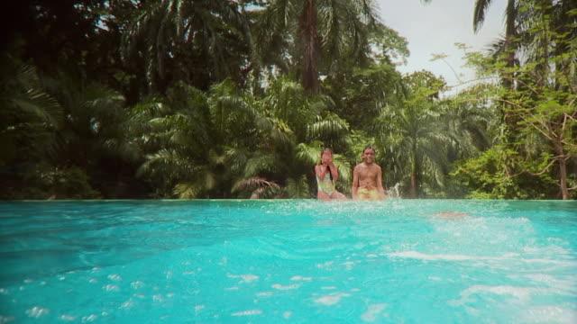 vídeos y material grabado en eventos de stock de ws boy (12-13) and girl (6-7) sitting and splashing from edge of pool, another boy joining them, panama city, panama  - bañador de natación