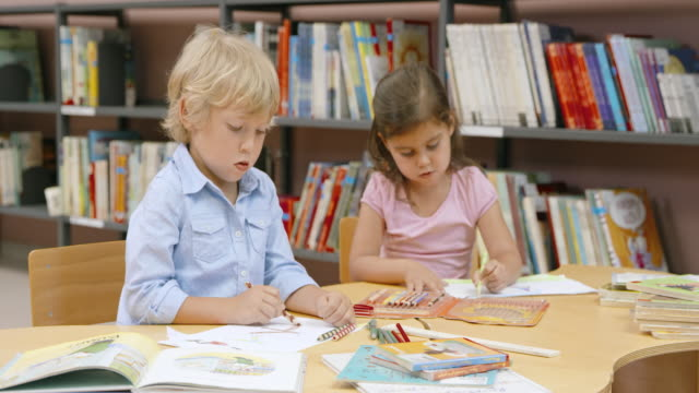 boy and girl sitting in library drawing with colored pencils - sharing stock videos & royalty-free footage