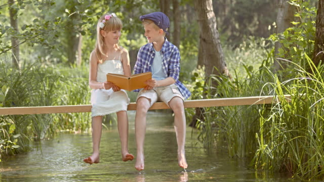 slo mo boy and girl sitting on footbridge and reading - little girls bare feet stock videos and b-roll footage
