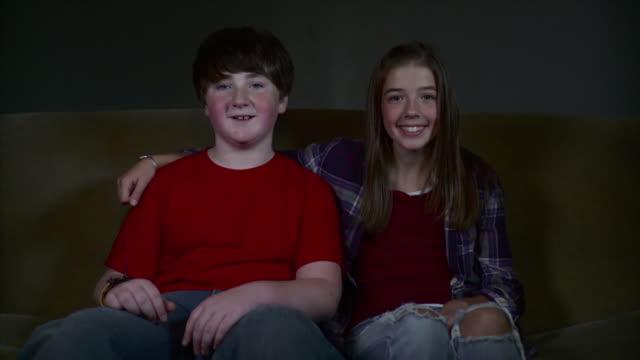 ms boy and girl (12-13) sitting on sofa and smiling / brooklyn, new york, usa - 12 13 år bildbanksvideor och videomaterial från bakom kulisserna