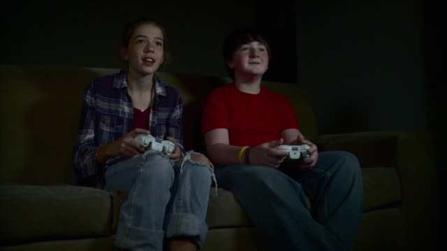 vídeos de stock e filmes b-roll de ms ds boy and girl (12-13) sitting on sofa playing video game / brooklyn, new york, usa - 12 13 anos
