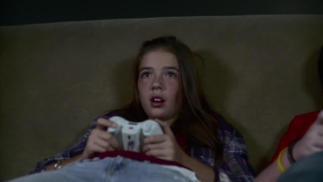 vídeos de stock, filmes e b-roll de ms ds boy and girl (12-13) sitting on sofa playing video game / brooklyn, new york, usa - menina