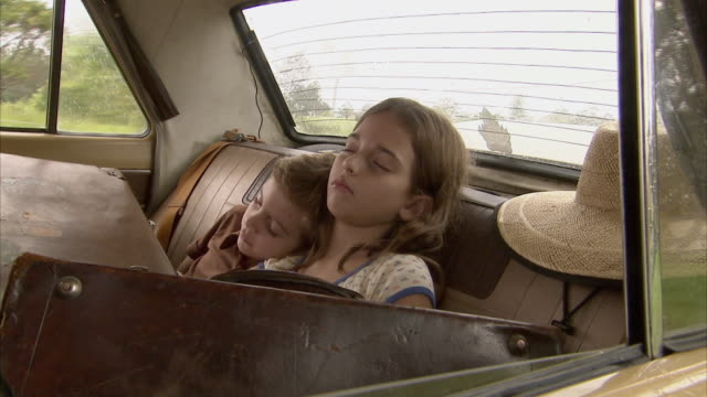 ms, boy (6-7) and girl (10-11) sleeping on car back seat, old fashion suitcases in foreground, tamborine mountain, brisbane, queensland, australia - 10 11 jahre stock-videos und b-roll-filmmaterial