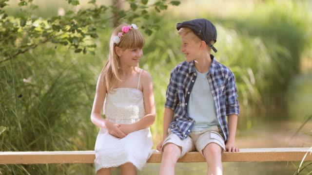SLO MO – Jungen und Mädchen in Baden Wasser sitzt auf Fußgängerbrücke