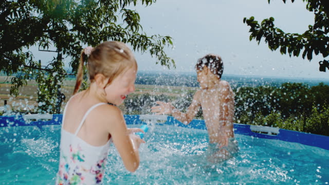 ms boy and girl splashing,playing with squirt gun in swimming pool - squirt gun stock videos and b-roll footage