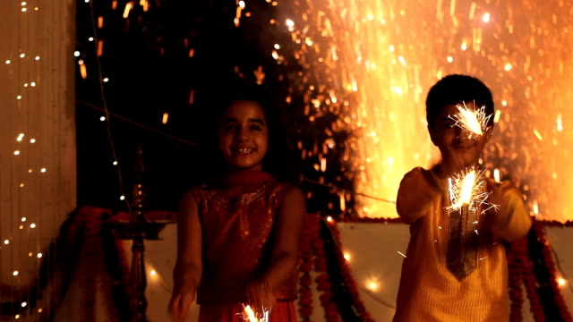 ms boy and girl standing together and enjoying sparklers in diwali festival - dress stock videos & royalty-free footage