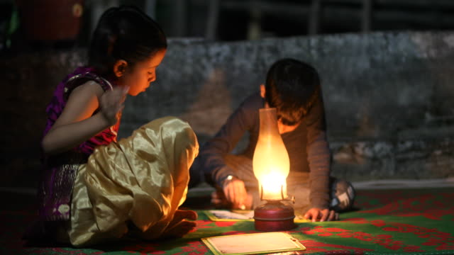 boy and girl studying in oil lamp - povertà video stock e b–roll