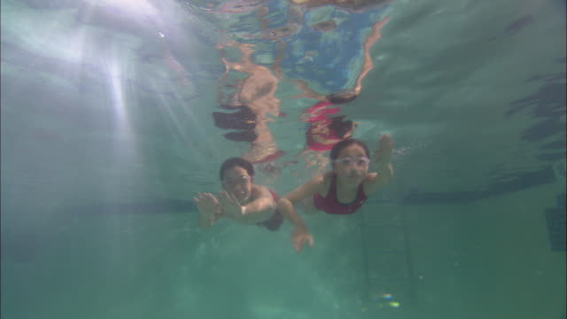 LA WS Boy and girl swimming above camera in pool and wearing swim goggles / Riverhead, New York, USA