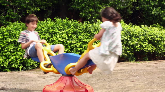 boy and girl swinging in a seesaw - wippe stock-videos und b-roll-filmmaterial