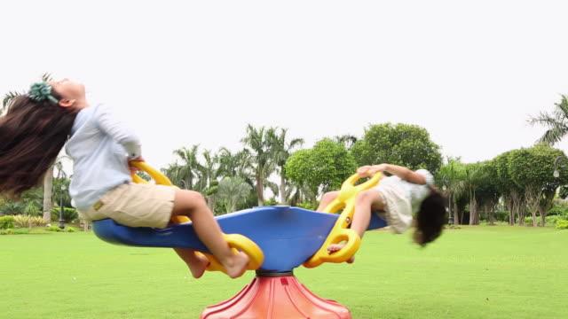vídeos y material grabado en eventos de stock de boy and girl swinging in a seesaw - balancín