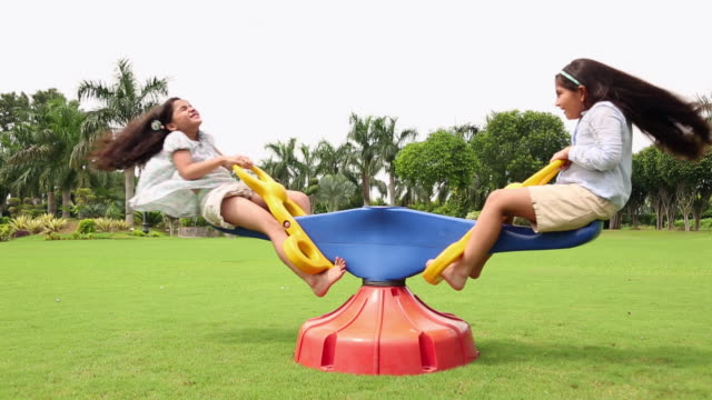 boy and girl swinging in a seesaw - kinderspielplatz stock-videos und b-roll-filmmaterial