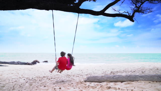 ws boy and girl swinging together by the sea - shorts stock videos & royalty-free footage