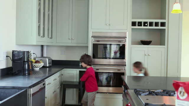 WS Boy (8-9) and girl (6-7) taking food from kitchen cabinet, Yarmouth, Maine, USA