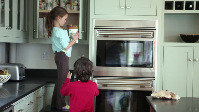 ms boy (8-9) and girl (6-7) taking food from kitchen cabinet, yarmouth, maine, usa - cabinet stock videos and b-roll footage