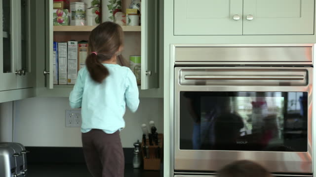 vídeos de stock, filmes e b-roll de ms boy (8-9) and girl (6-7) taking food from kitchen cabinet, yarmouth, maine, usa - cabinet