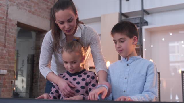 jungen und mädchen unterricht um synthesizer zu spielen - akkord stock-videos und b-roll-filmmaterial