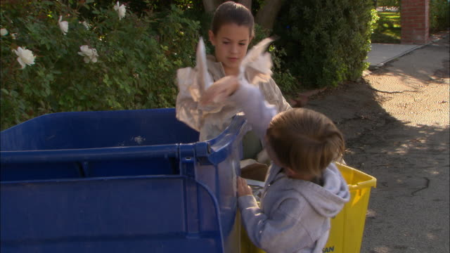 MS, Boy (4-5) and girl (10-11) throwing garbage into recyclable bin, Los Angeles, California, USA