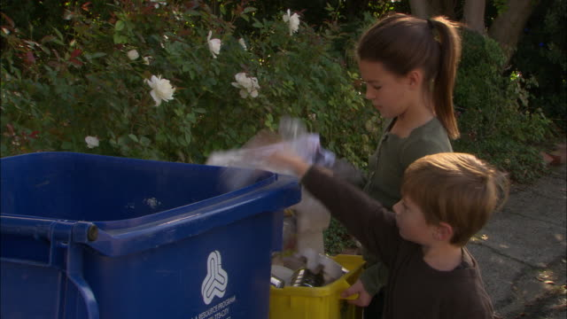vídeos de stock, filmes e b-roll de ms, boy (4-5) and girl (10-11) throwing garbage into recyclable bin, los angeles, california, usa - reciclagem