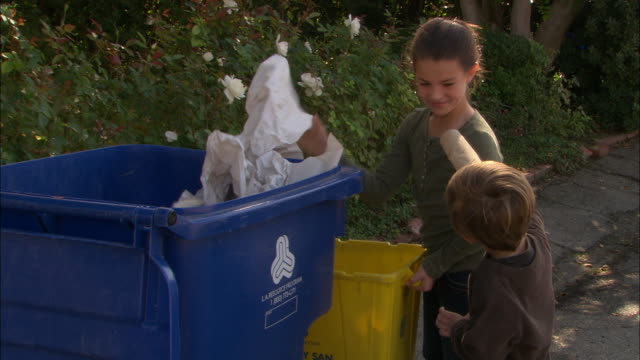 CU, MS, Boy (4-5) and girl (10-11) throwing garbage into recyclable bin, Los Angeles, California, USA