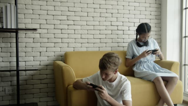 boy and girl using interesting app video game on the smartphone - handheld video game stock videos & royalty-free footage