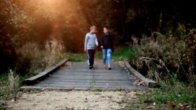 boy and girl walking across wooden bridge