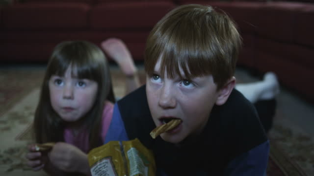 cu boy (10-11) and girl (2-3) watching television and eating snacks, american fork, utah, usa - unhealthy eating 個影片檔及 b 捲影像