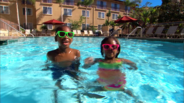 ms, boy (6-7) and girl (8-9) wearing sunglasses playing in swimming pool, carlsbad, california, usa - carlsbad california stock videos & royalty-free footage