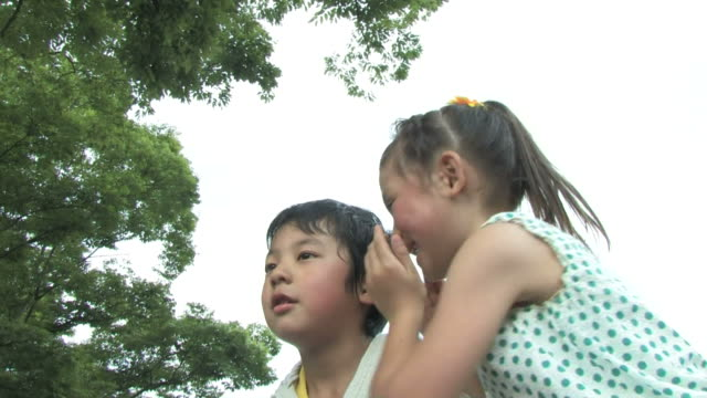 Boy and girl whispering into each other's ear