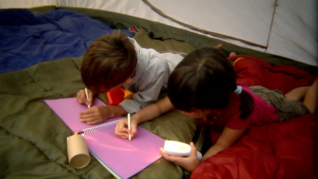 MS Boy and girl writing in notebook by flashlight in tent/ Bovina, New York