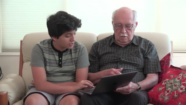 vídeos de stock e filmes b-roll de boy and grandfather on sofa with computer - idoso na internet
