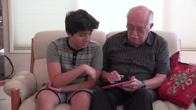 stockvideo's en b-roll-footage met boy and grandfather using a tablet - oudere internetgebruiker