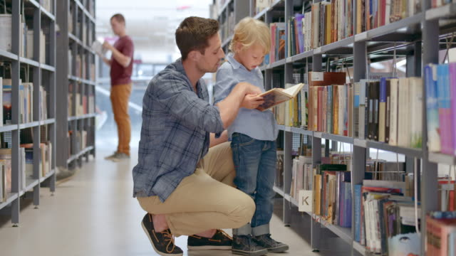DS Boy and his dad reading a book in the library aisle