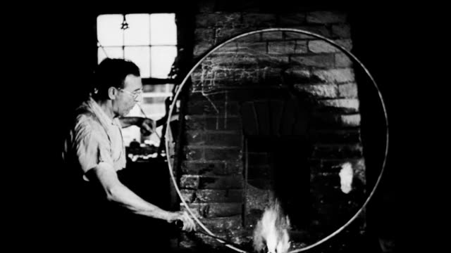 stockvideo's en b-roll-footage met / boy and his dog walk into barn / man works on creating wagon wheel casings out of metal next to blacksmith fire / cu molten metal sparking... - smeden