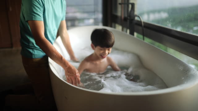 boy and his father enjoying bubble bath in bathtub - vasca da bagno video stock e b–roll