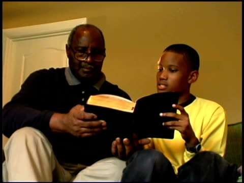 a boy and his grandfather read the bible together. - tre quarti video stock e b–roll