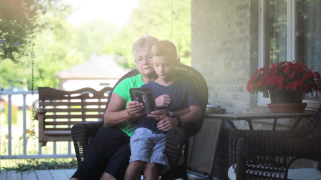 boy and his grandmother playing game on wireless tablet - enkelin stock-videos und b-roll-filmmaterial