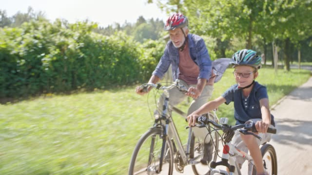 ts boy and his grandpa riding their bikes fast in the sunny park - 60 64 years stock videos & royalty-free footage