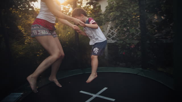 boy and his mom on a trampoline - carefree stock videos & royalty-free footage